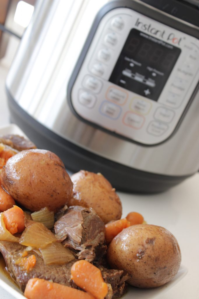 instant pot pot roast with vegetables on a plate with Instant Pot in the background