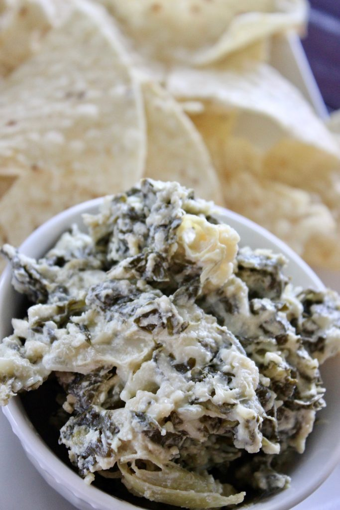 crockpot spinach artichoke dip in a white bowl with tortilla chips