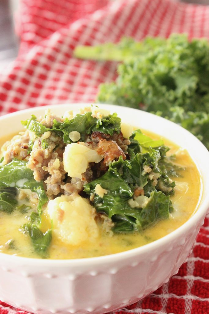 Copycat Olive Garden zuppa toscana soup with cauliflower in a white bowl on a red towel to make it Keto friendly
