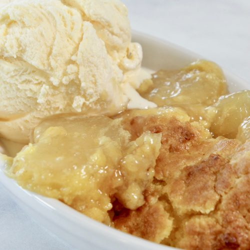 Crock Pot Apple Dump Cake in a dish with ice cream