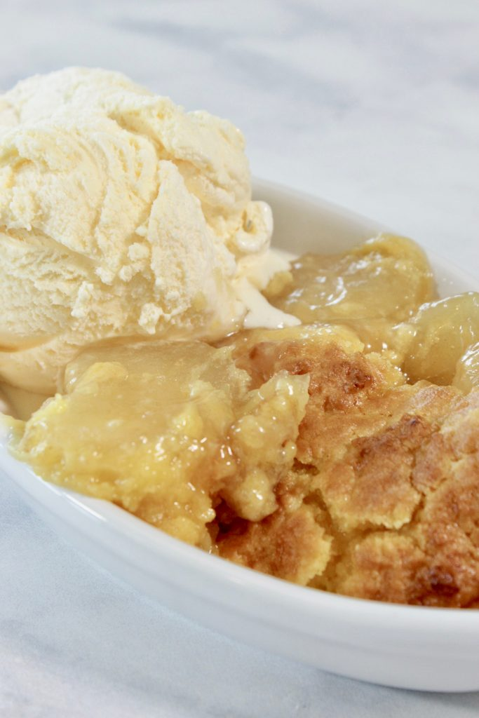 Crock Pot Apple Dump Cake in a dish with ice cream