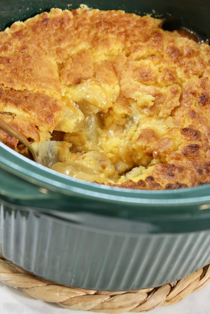 Apple dump cake in the crock pot with one serving out of it
