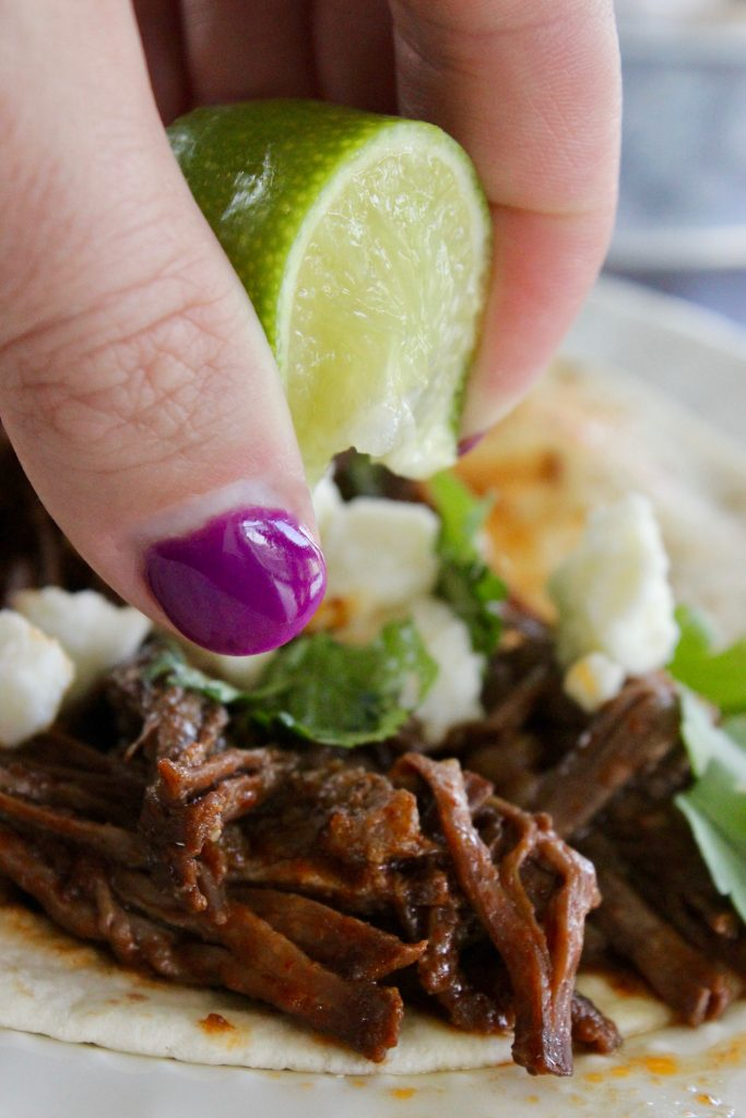 Squeezing a lime on the crock pot shredded beef that I turned into tacos