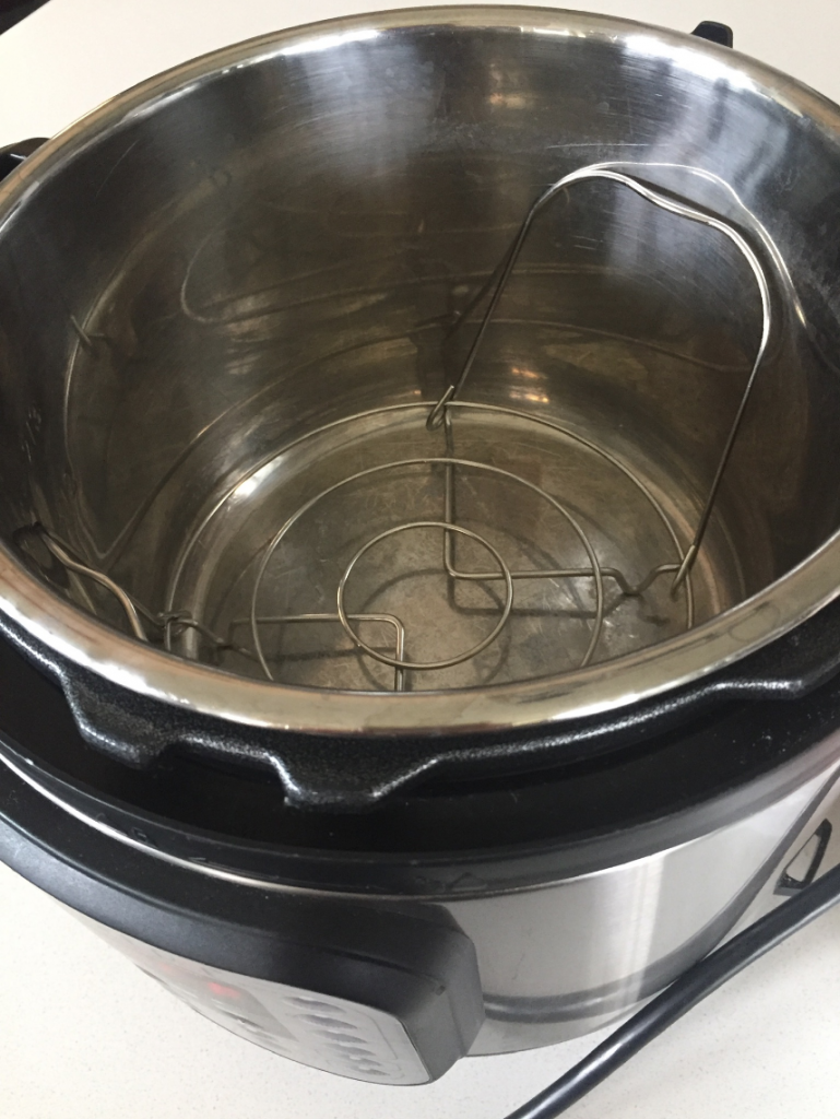 metal trivet in Instant Pot getting ready to put chicken wings in the Instant Pot