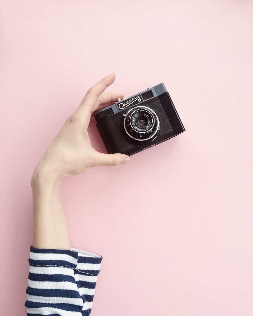 camera taking food pictures on pink background