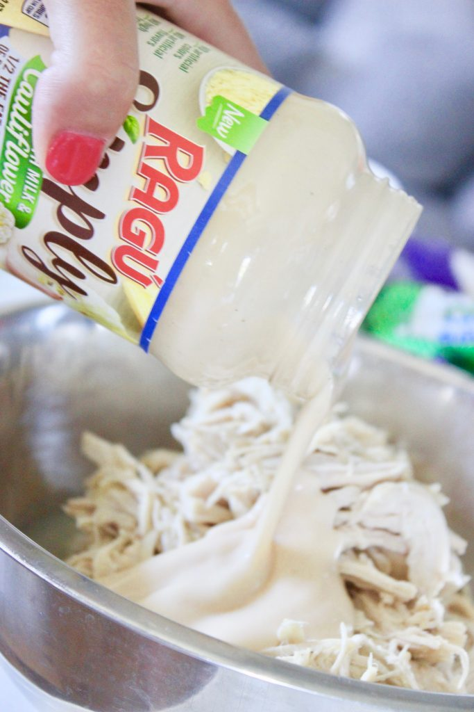 RAGÚ Simply Creamy ALfredo Sauce being used in Chicken Alfredo Lasagna
