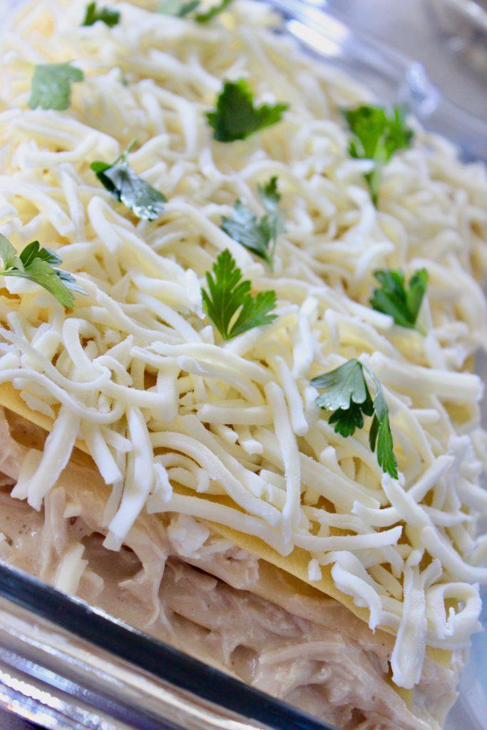 chicken alfredo lasagna in a clear baking dish