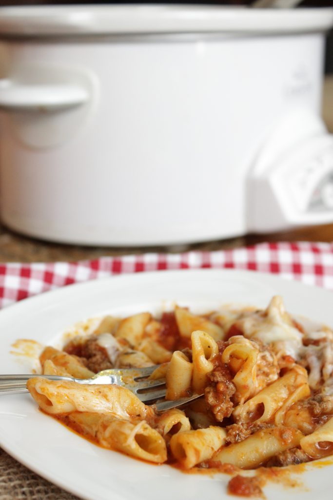 Crock Pot Baked Ziti in a white bowl with a slow cooker in the background