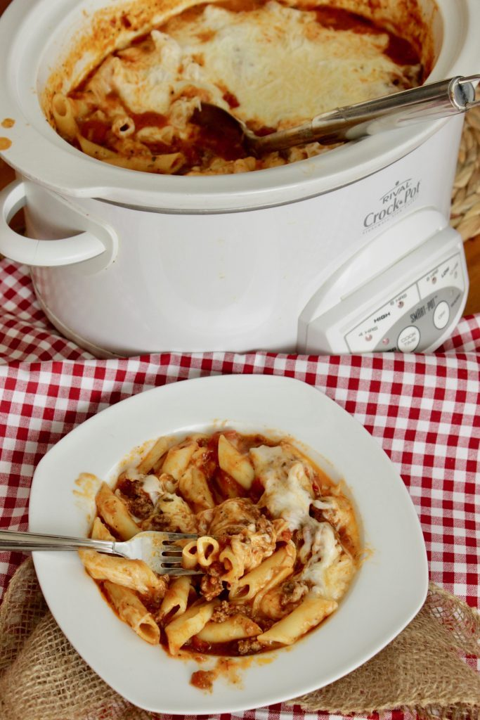 Crock Pot baked ziti in a bowl with the full slow cooker behind the bowl of crock pot ziti