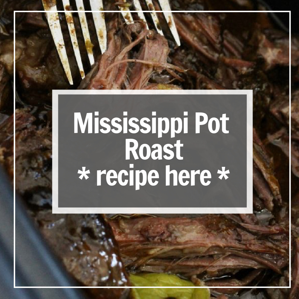 Mississippi pot roast with pepperoncini peppers and forks shredding the roast in the crock pot