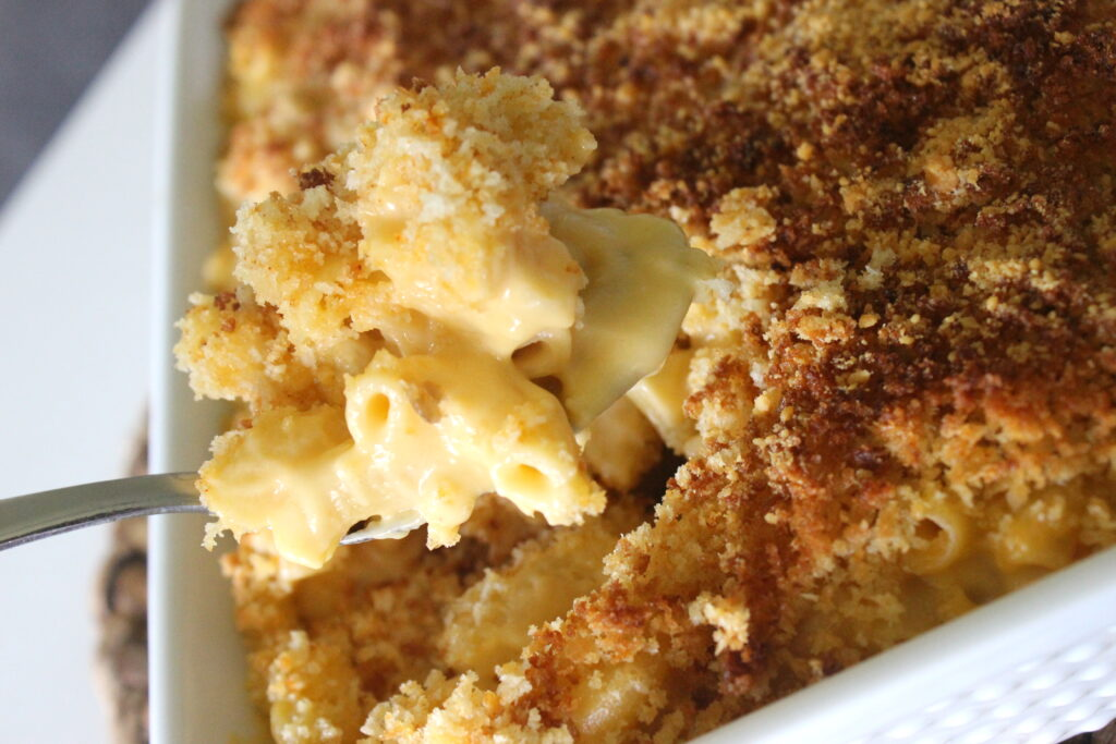Spoonful of baked macaroni and cheese in a white dish