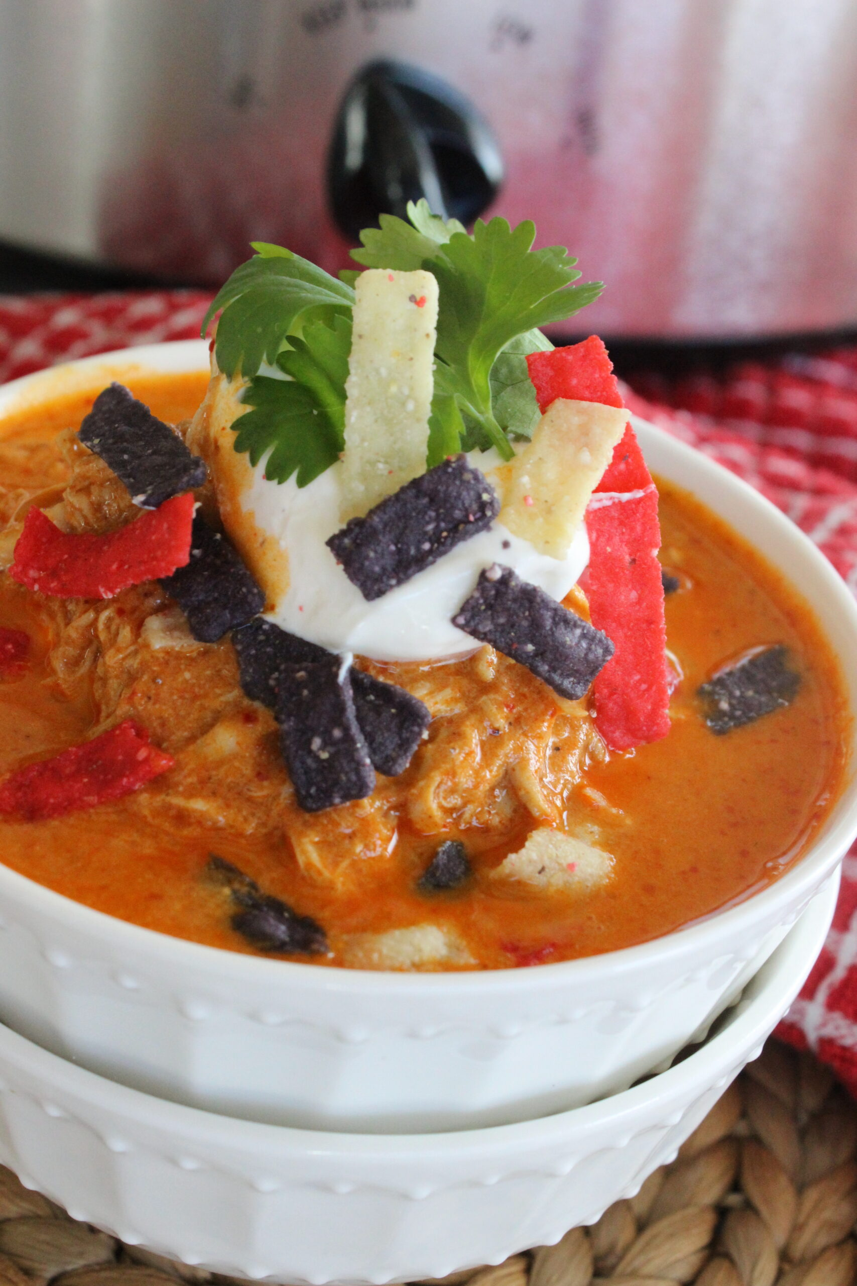 Creamy chicken enchilada soup in a bowl with sour cream
