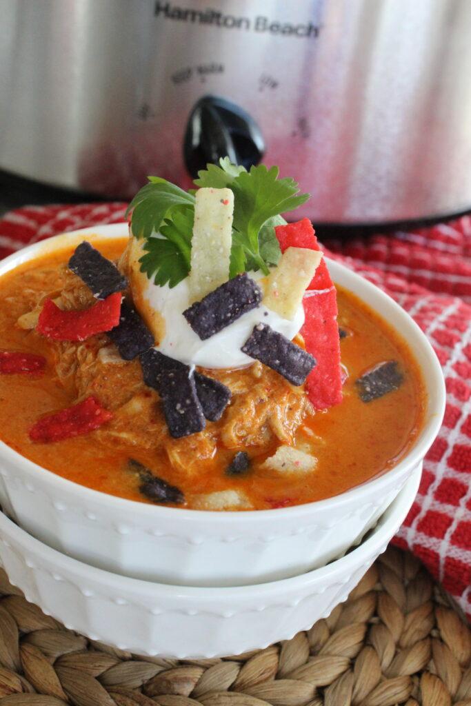 creamy chicken enchilada soup in a white bowl