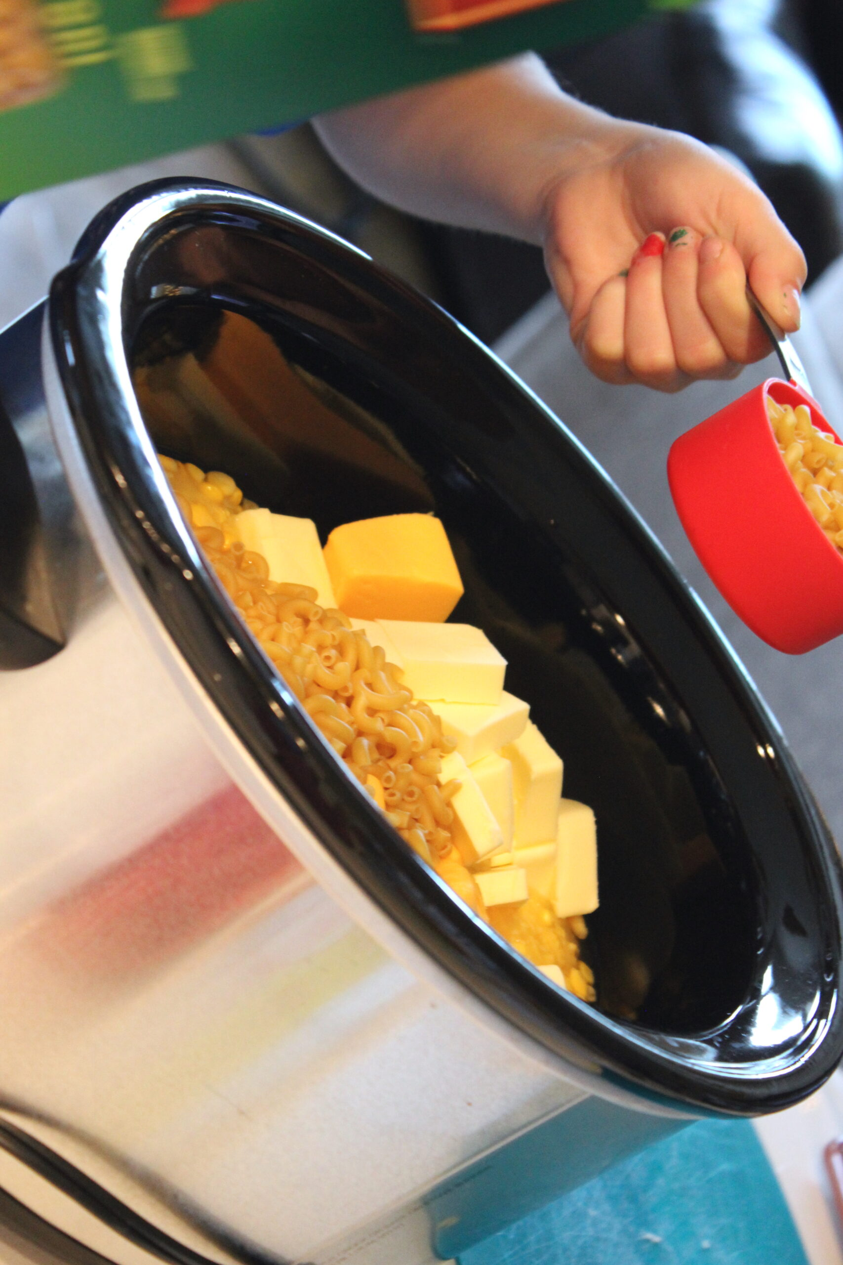 girl putting macaroni into crock pot
