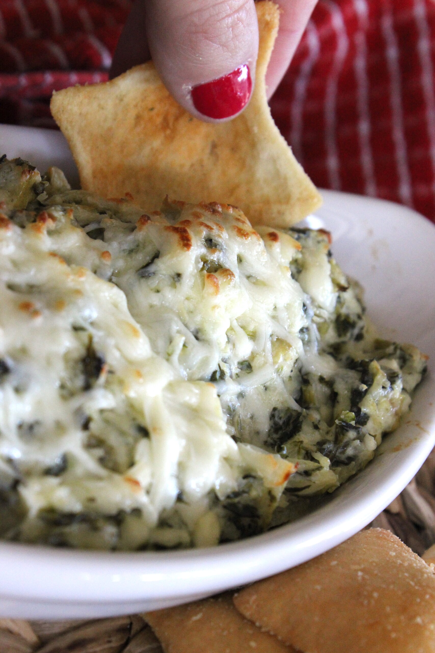 mozzarella cheese on top of spinach and artichoke dip on a pita chip